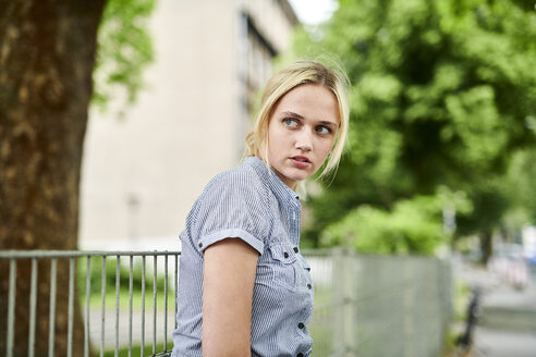 Serious blond young woman at a fence - MMIF00153