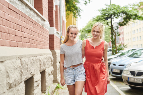 Two happy young women walking in the city together - MMIF00162