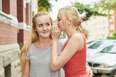 Two young women in the city whispering - MMIF00165