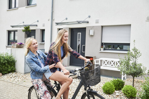 Two happy young women riding bicycle together on one bike - MMIF00171