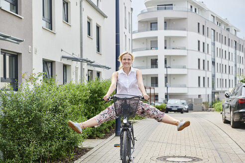 Happy young woman riding bicycle in housing area - MMIF00174