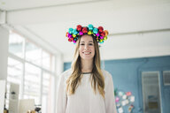 Portrait of smiling woman with colourful Christmas bauble wreath on her head - MOEF01330