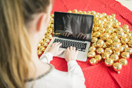 Woman sitting at table with many golden Christmas baubles working on laptop - MOEF01333