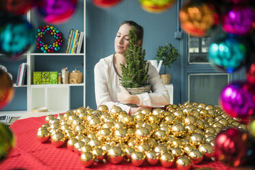 Woman sitting at table with many golden Christmas baubles holding potted fir tree - MOEF01336