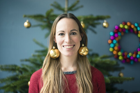 Portrait of smiling woman wearing golden Christmas baubles earrings - MOEF01339