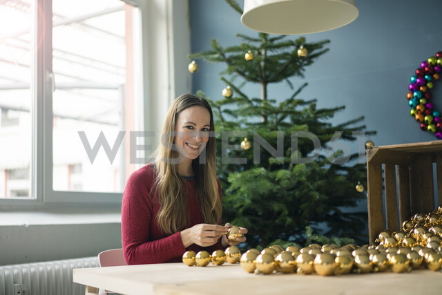 Portrait of smiling woman sitting at table with many golden Christmas baubles - MOEF01342