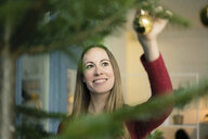 Portrait of smiling woman decorating Christmas tree - MOEF01345