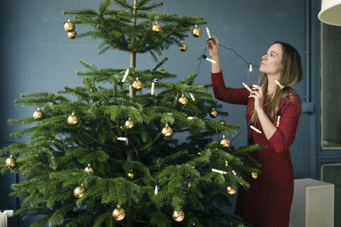 Woman decorating Christmas tree - MOEF01351