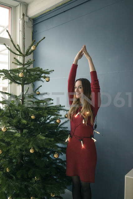 Portrait of smiling woman standing besides Christmas tree - MOEF01354