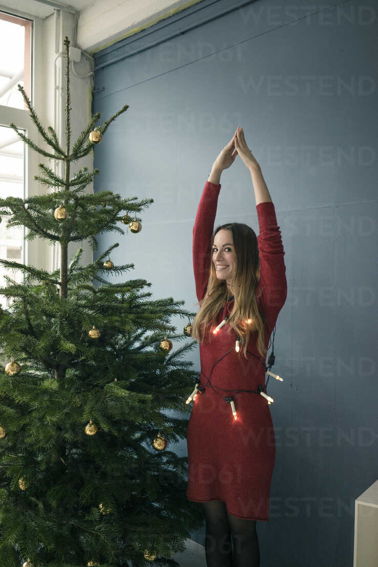 Portrait of smiling woman standing besides Christmas tree - MOEF01354 - Robijn Page/Westend61