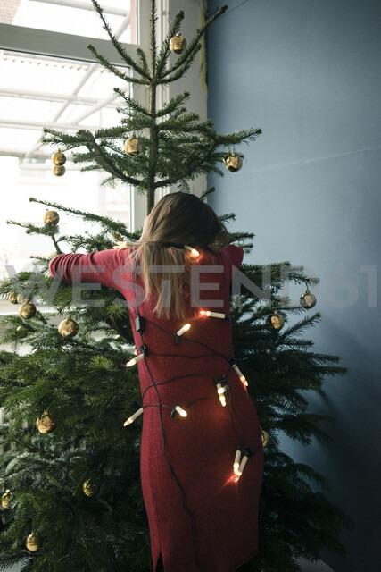 Back view of woman hugging Christmas tree - MOEF01357