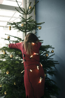 Back view of woman hugging Christmas tree - MOEF01357
