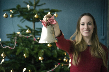 Smiling woman showing silver   Christmas bell - MOEF01363