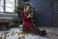 Smiling woman sitting on wooden box in front of decorated Christmas tree using tablet - MOEF01366
