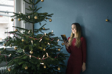 Smiling woman with tablet standing besides decorated Christmas tree - MOEF01369