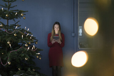 Smiling woman in a loft using tablet at Christmas time - MOEF01372