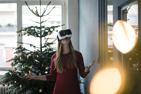 Woman using Virtual Reality Glasses at Christmas time - MOEF01375