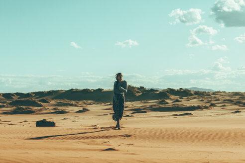 Young woman walking in desert landscape - OCAF00260