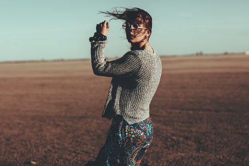Young woman with windswept hair standing in desert landscape - OCAF00266