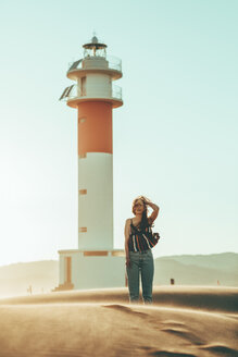 Young woman with windswept hair standing in desert landscape at lighthouse - OCAF00269