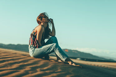 Young woman sitting in desert landscape - OCAF00272