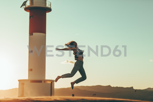 Young woman jumping in desert landscape at lighthouse - OCAF00275 - Oriol Castelló Arroyo/Westend61
