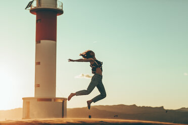 Young woman jumping in desert landscape at lighthouse - OCAF00275