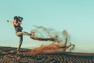 Young woman kicking sand in desert landscape - OCAF00278