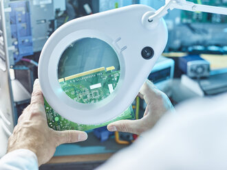 Technician checking circuit board with magnifier - CVF00704