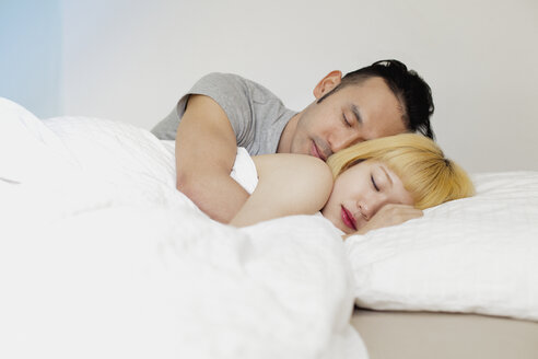 Young couple sleeping on bed against wall at home - FSIF03150