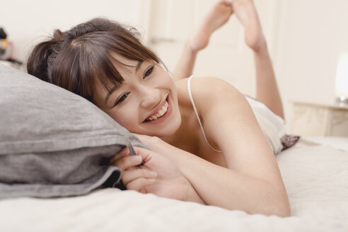Thoughtful happy young woman lying on bed at home - FSIF03153