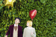 Couple looking at balloon while standing against plants - FSIF03156