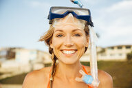 Portrait of woman wearing snorkel looking at camera smiling - ISF09255
