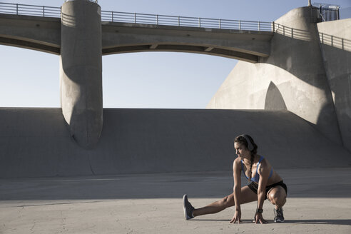 Female athlete with headphones, stretching, Van Nuys, California, USA - ISF09282