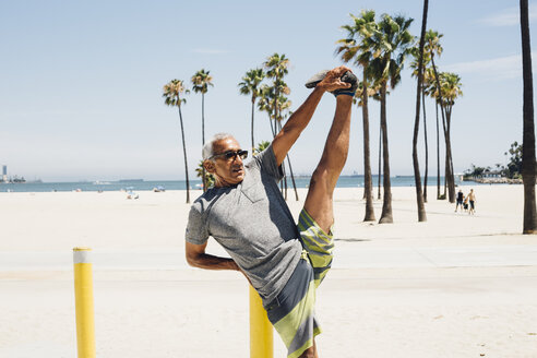 Senior man, exercising on beach, stretching leg, Long Beach, California, USA - ISF09324