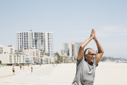 Senior man, exercising on beach, in yoga position, Long Beach, California, USA - ISF09327