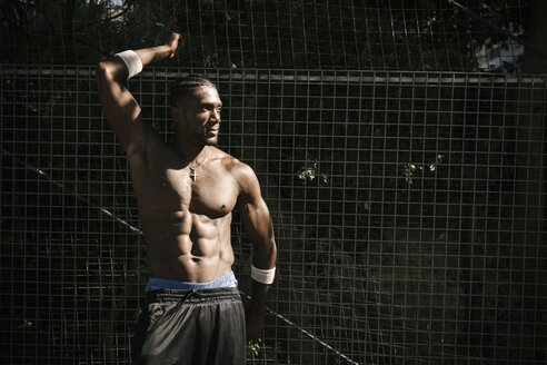Bare-chested muscular young man posing by wire fence - CUF23184