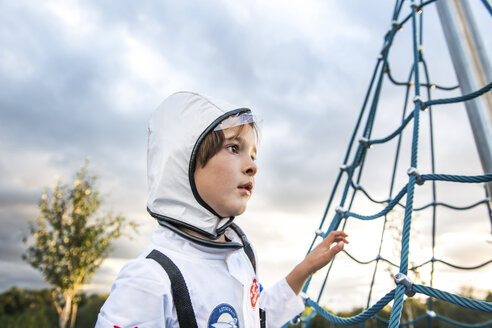 Portrait of boy in astronaut costume gazing by playground climbing frame - CUF23193