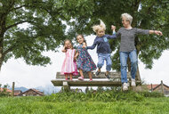 Grandmother and grandchildren in mid air jumping from park bench, Fuessen, Bavaria, Germany - CUF23247
