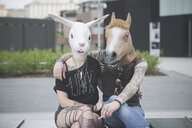 Portrait of punk hippy couple wearing rabbit and horse costume masks - CUF23253