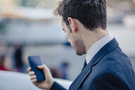 Over the shoulder view of businessman texting on smartphone - CUF23316