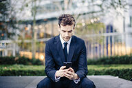 Businessman reading smartphone texts in front of office - CUF23325