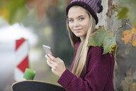 Portrait of smiling teenage girl with cell phone and skateboard - ZEF15596