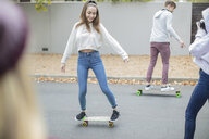 Happy teenage friends riding skateboard on the street - ZEF15608