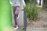 Close-up of boy holding skateboard and using cell phone - ZEF15611