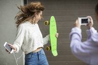 Friend taking picture of carefree teenage girl dancing while holding skateboard and listening to music - ZEF15614