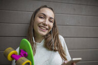 Portrait of smiling teenage girl with cell phone, earphones and skateboard - ZEF15617