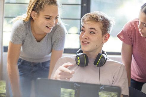Teenage girls talking to boy using laptop - ZEF15626