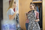 Two smiling teenage girls choosing clothes from wardrobe - ZEF15632