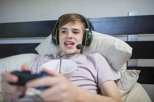 Boy lying in bed playing video game - ZEF15647